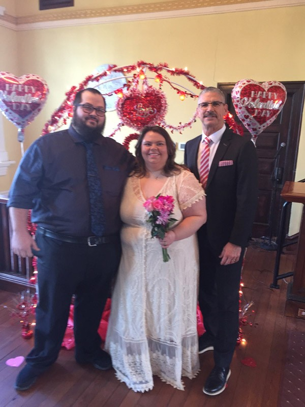 Marriage ceremony 2020 - happy couple standing with Clerk Dale Cross